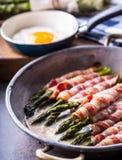 Espargos Bacon do aspargo e do rolo Aspargo grelhado com bacon e o ovo frito rolados Bandeja velha fritada completamente do bacon foto de stock