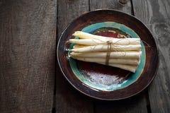 Espargos brancos Um grupo dos vegetais em uma placa cer?mica foto de stock