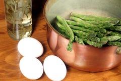 Espargos no potenciômetro de cobre com ovos e frasco do vinagre fotografia de stock royalty free