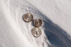 Espèces froides - pièces en argent dans la neige Image stock