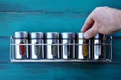 Especia de vuelta de la mano del cocinero en un estante de especia Fotografía de archivo libre de regalías