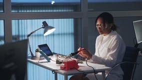 Especialista afroamericano de la electrónica que hace pruebas en tablero electrónico con el probador del multímetro en laboratori almacen de metraje de vídeo