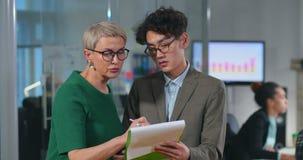 Especialista asiático joven que consulta con su jefe almacen de metraje de vídeo