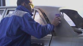 Especialista auto joven que pule el coche con los vidrios y el uniforme especiales en servicio moderno del coche almacen de video