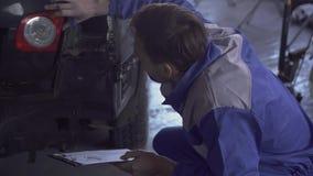 Especialista auto que hace un examen del coche después de un accidente, datos de reparación de la grabación de la suspensión de l almacen de video