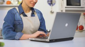 Especialista culinario de sexo femenino que mecanografía en el ordenador portátil, guardando el blog, dando cocinando extremidade almacen de video