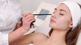 Especialista da cosmetologia que aplica a m?scara facial usando a escova, fazendo a pele hidratada e saud?vel Mulher atrativa que video estoque