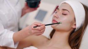 Especialista da cosmetologia que aplica a m?scara facial usando a escova, fazendo a pele hidratada e saud?vel Mulher atrativa que filme