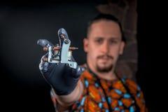 Especialista da tatuagem e uma máquina da tatuagem em seu salão de beleza Imagens de Stock Royalty Free