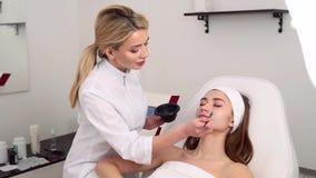 Especialista de la cosmetolog?a que aplica la m?scara facial usando cepillo, haciendo la piel hidratada y sana Mujer atractiva qu almacen de video