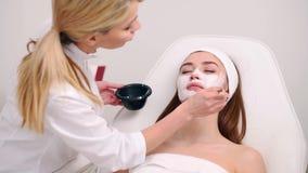 Especialista de la cosmetolog?a que aplica la m?scara facial usando cepillo, haciendo la piel hidratada y sana Mujer atractiva qu almacen de metraje de vídeo