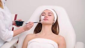 Especialista de la cosmetolog?a que aplica la m?scara facial usando cepillo, haciendo la piel hidratada y sana Mujer atractiva qu metrajes