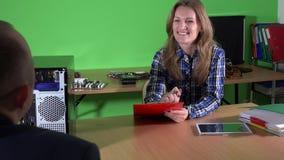 Especialista de la reparación del ordenador y cliente femeninos del varón con el ordenador quebrado de la PC almacen de video