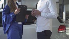 Especialista de sexo femenino del automóvil después de tomar los datos sobre el coche y firmados tomando llave y sacudiendo la ma metrajes
