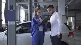 Especialista de sexo femenino del automóvil que toma datos sobre el coche para la inspección del hombre atractivo joven en servic almacen de video