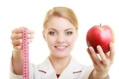 Especialista del doctor que sostiene la manzana de la fruta y la cinta de la medida fotografía de archivo