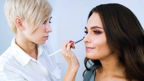 Especialista del salón de belleza que hace el maquillaje profesional para la mujer morena joven imagen de archivo libre de regalías