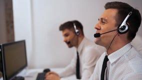 Especialista do apoio do centro de chamada de dois homens que fala com os clientes por auriculares video estoque