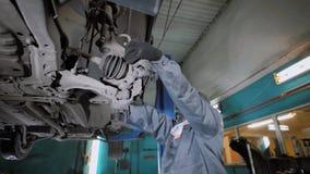 Especialista em um sercvice do carro que verifica os freios em um veículo vídeos de arquivo