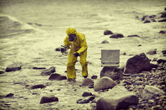 Especialista en el traje protector que lleva la muestra de agua el envase imagenes de archivo