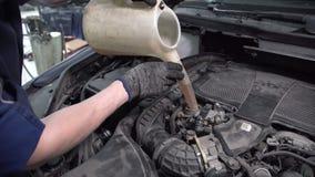 Especialista a estação do serviço para preencher o óleo usando uma lata molhando vídeos de arquivo