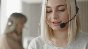 Especialista fêmea do apoio do centro de chamada dois que fala com os clientes por auriculares vídeos de arquivo