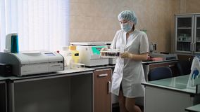 Especialista fêmea que gira sobre o centrifugador Especialista fêmea no uniforme branco que gira sobre o centrifugador com o espé vídeos de arquivo