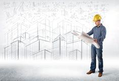 Especialista hermoso de la construcción con el dibujo de la ciudad en fondo Fotos de archivo