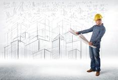 Especialista hermoso de la construcción con el dibujo de la ciudad en fondo Fotografía de archivo libre de regalías