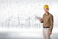 Especialista hermoso de la construcción con el dibujo de la ciudad en fondo Imagen de archivo libre de regalías
