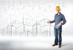 Especialista hermoso de la construcción con el dibujo de la ciudad en fondo Foto de archivo
