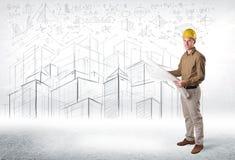 Especialista hermoso de la construcción con el dibujo de la ciudad en fondo Foto de archivo libre de regalías