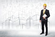 Especialista hermoso de la construcción con el dibujo de la ciudad en fondo Imagen de archivo