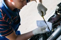 Especialista na manutenção do carro, verificações o nível de óleo do motor do carro fotos de stock