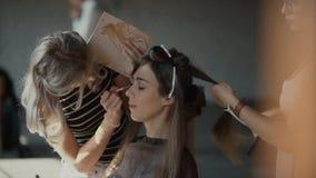 Especialista que hace el maquillaje para el modelo Apacible compense a la chica joven Demostración de modelos metrajes