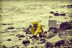 Especialista que lleva la muestra de agua el envase en orilla rocosa fotografía de archivo
