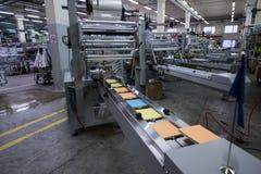 Especialista que trabaja en la máquina para los trapos de empaquetado Foto de archivo libre de regalías