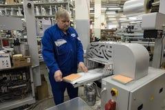 Especialista que trabaja en la máquina para los trapos de empaquetado Fotos de archivo