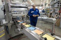 Especialista que trabaja en la máquina para los trapos de empaquetado Imagenes de archivo