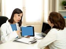 Especialista sonriente del doctor de la mujer que tiene consulta usando la tableta digital para informar al paciente fotos de archivo libres de regalías