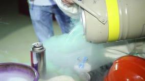 Especialista Working com nitrogênio líquido Transfusão do nitrogênio no tanque O vapor da reação com o ar vídeos de arquivo