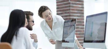 Especialistas de la compañía que discute horario financieros en el escritorio imagen de archivo libre de regalías