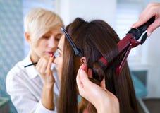 Especialistas do salão de beleza que fazem a composição e o penteado profissionais usando o ferro de ondulação para a jovem mulhe fotografia de stock
