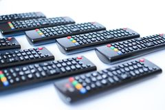 Especially heavily blurred black remote controls for the TV on a white background stock photo