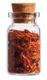 Especiaria do açafrão em uma garrafa pequena isolada no branco Foto de Stock
