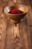 Especiaria do açafrão na bacia do produto de cerâmica no backgro de madeira textured velho Fotos de Stock Royalty Free