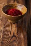Especiaria do açafrão na bacia do produto de cerâmica no backgro de madeira textured velho Imagens de Stock