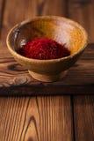 Especiaria do açafrão na bacia do produto de cerâmica no backgro de madeira textured velho Fotografia de Stock Royalty Free
