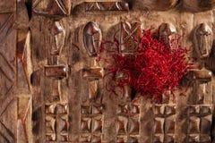 A especiaria do açafrão na pilha no vintage cinzelou o fundo de madeira Fotografia de Stock Royalty Free