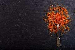 Especiaria secada do açafrão em uma colher no fundo escuro Foto de Stock Royalty Free